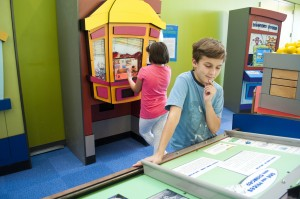 Two children play a game and read an exhibit