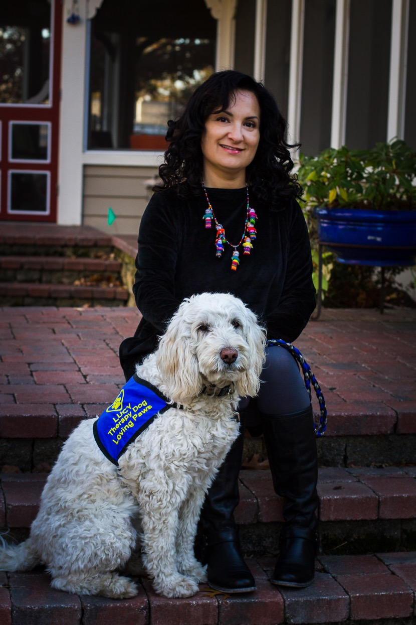 Lucy the therapy dog and her owner sitting on steps in front of a home