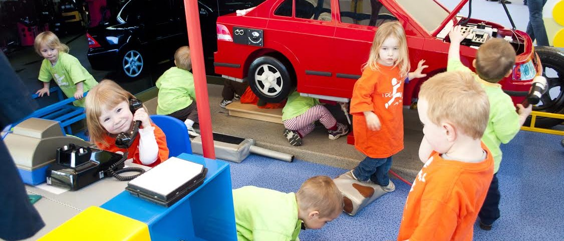 A group of children playing in the mechanic exhibit