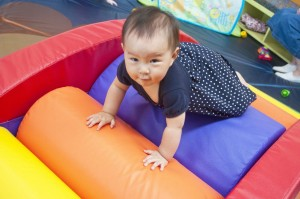 Baby climbs on a multicolored climber in the infant area