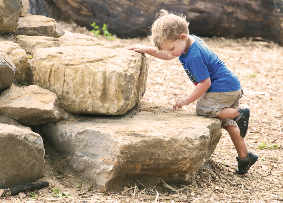 A small child inspects a rock while getting ready to climb the rock