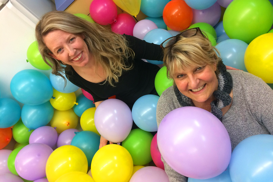 two KCDC staff members pose in a pile of balloons
