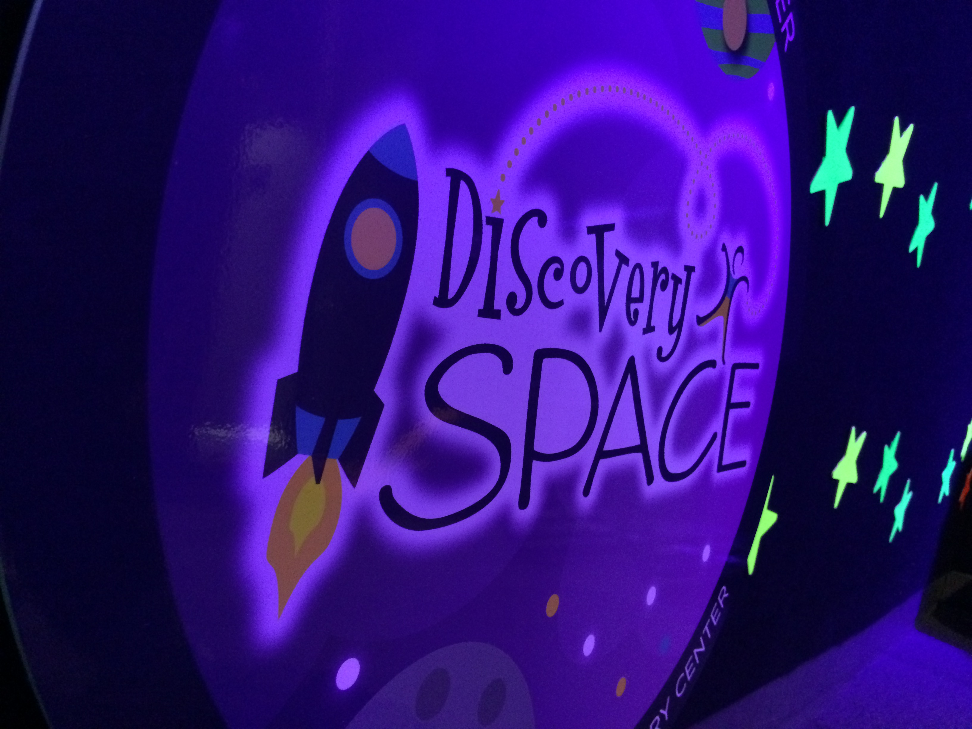 Discovery Space logo next to glow in the dark stars attached to the velcro wall and glowing in blacklight