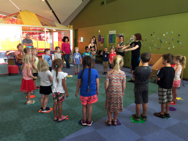 Children standing in a circle learning from a ballet instructor at the Kansas Children's Discovery Center