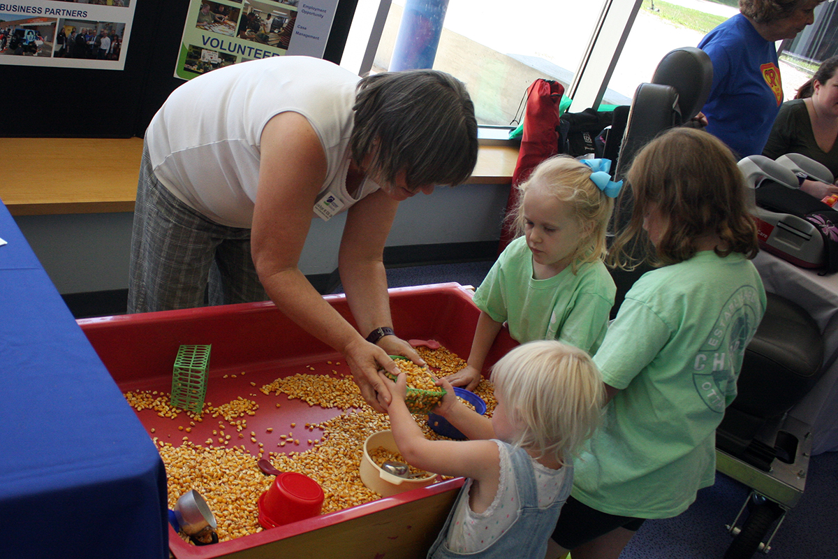 children play with corn in a red bin