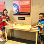 Kids using rolling pins to roll out dough in the house portion of the Kenya's Kids exhibit.