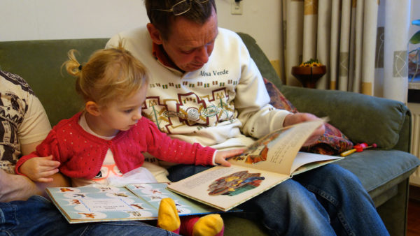 a little girl sits next to her grandpa and they both have books open on their lap