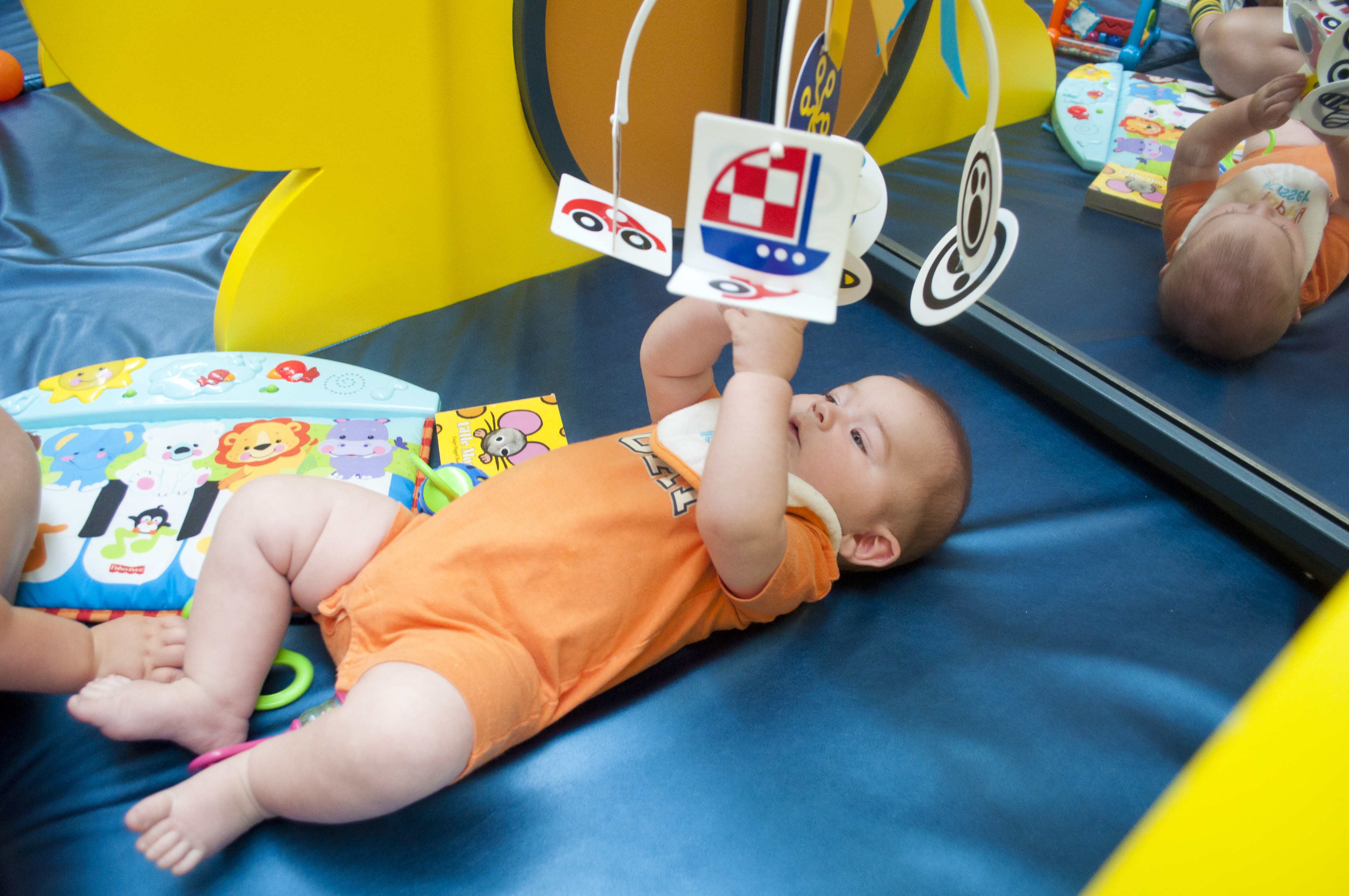An infant plays with a mobile on a blue mat in the infant area