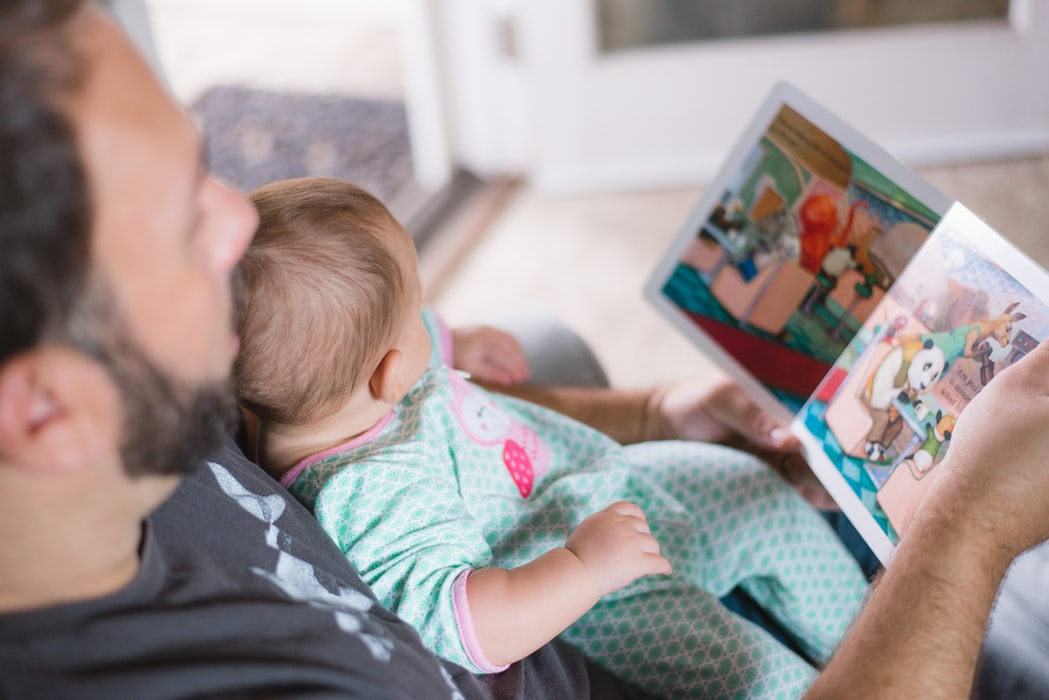 A baby sits on their dads lap while he reads a book