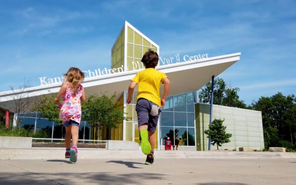 Two children run towards KCDC on a nice sunny day, the girl wears a pink dress and the boy a yellow shirt