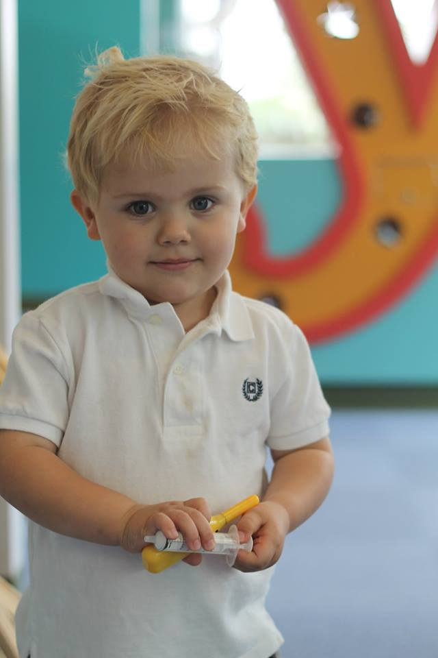Closeup of a blonde boy holding toys