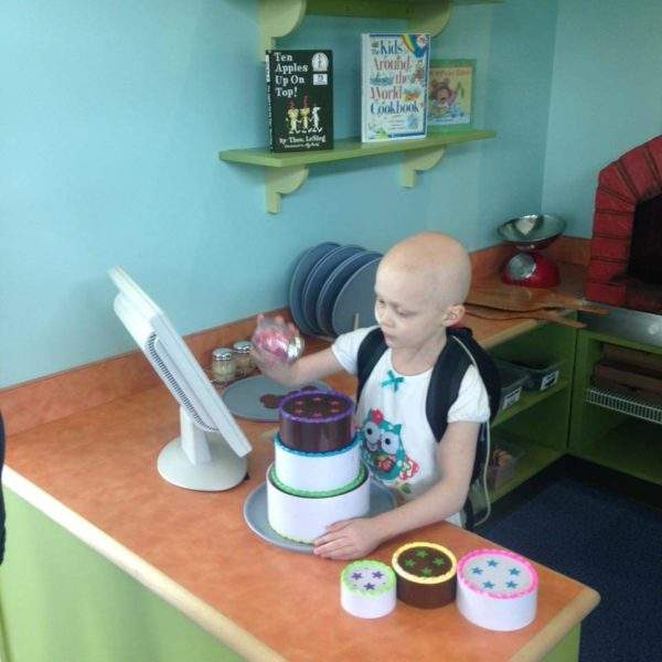 A child with no hair due to a medical condition plays with a pretend cake in the cafe exhibit
