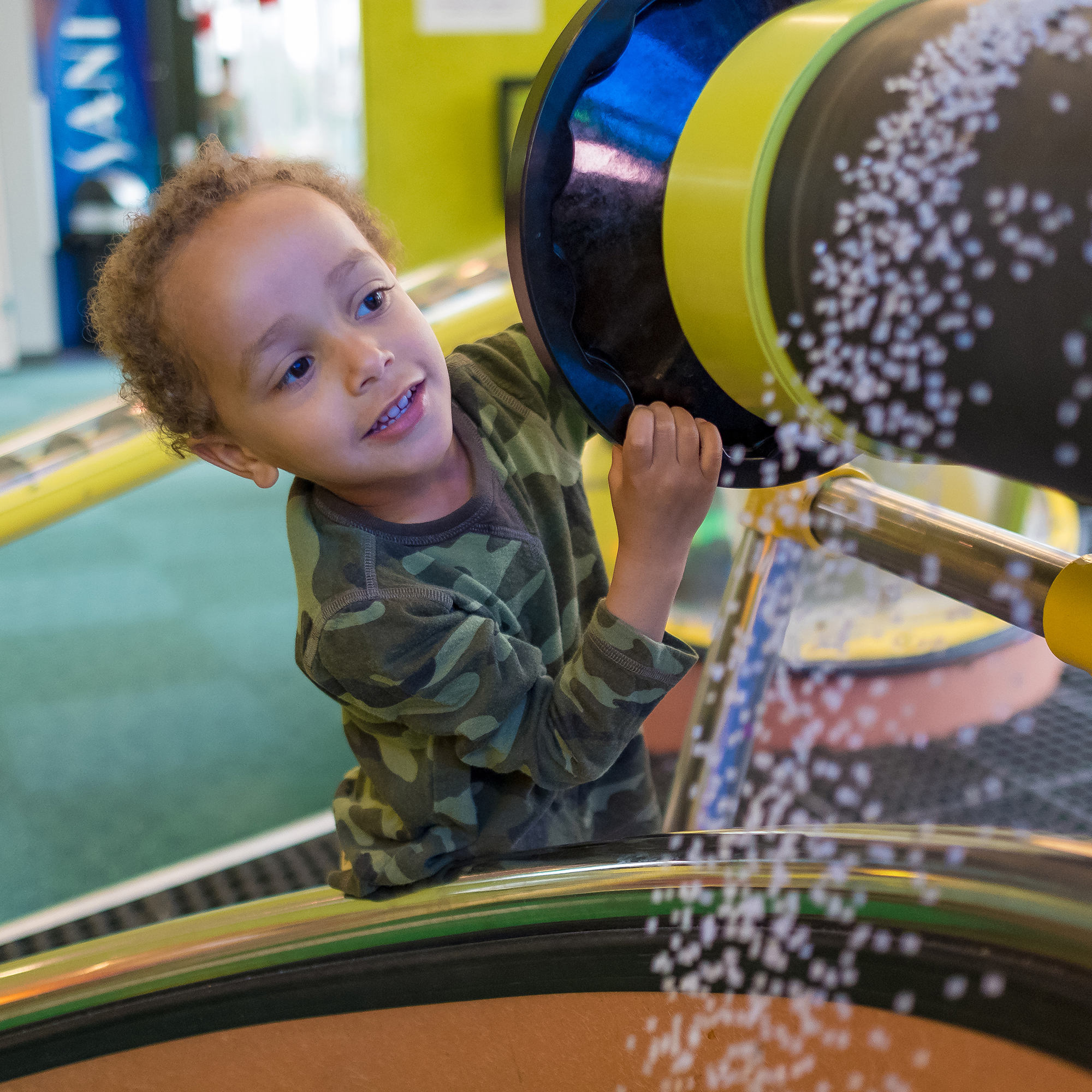 Small boy turns a wheel while white pellets fall over the edge
